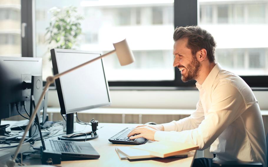 Bild på en man som sitter och arbetar framför en datorskärm